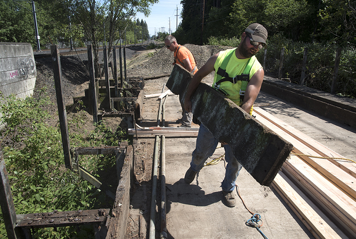 Workers for Benchmark Contracting prepare for structural upgrades to an old railroad trestle that will be part of the connection between the Westside Regional Trail and Waterhouse Trail.